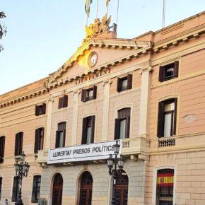 Concejales de Ciudadanos (Cs) colocan una bandera española en una ventana de la fachada del Ayuntamiento de Sabadell